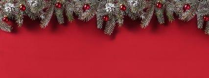 Cadre créatif de disposition fait de branches de sapin de Noël, cônes de pin, cadeaux, décoration rouge sur le fond rouge photographie stock