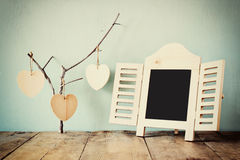 Cadre décoratif de tableau et coeurs accrochants en bois au-dessus de table en bois préparez pour le texte ou la maquette rétro i Image libre de droits