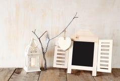 Cadre décoratif de tableau et coeurs accrochants en bois au-dessus de table en bois préparez pour le texte ou la maquette rétro i Photographie stock libre de droits