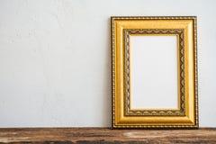 Cadre d'or de photo de vintage sur la vieille table en bois au-dessus du mur blanc b photographie stock libre de droits