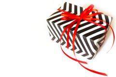 Cadre de cadeau Zigzag blanc noir Fond blanc, ruban rouge Photographie stock libre de droits