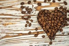 Cadre de café de coeur fait de grains de café sur la texture en bois Image libre de droits