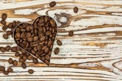 Cadre de café de coeur fait de grains de café sur la texture en bois Photo libre de droits