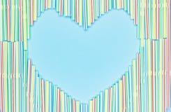 Cadre de coeur des pailles ou des tubules en plastique colorés de cocktail sur le fond bleu-clair avec le spase de copie photographie stock libre de droits