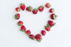 Cadre de coeur fait de fraises sur le fond blanc Configuration plate, vue supérieure, l'espace de copie, centré photos libres de droits