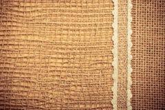 Cadre de dentelle sur le fond de tissu de toile de jute Photo libre de droits