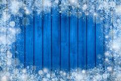 Cadre de fond de Noël avec la neige et le flocon de neige décorations de nouvelle année sur le fond en bois bleu images libres de droits