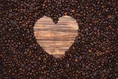 Cadre de forme de coeur des grains de café sur le fond en bois Images libres de droits