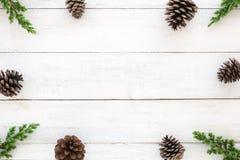 Cadre de Hristmas fait de feuilles de sapin et éléments rustiques de décoration de cônes de pin sur en bois blanc Photographie stock