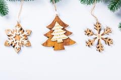 Cadre de Noël avec les branches de l'arbre de Noël et des décorations en bois sur le fond blanc Composition simple W en Noël Image stock