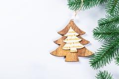 Cadre de Noël avec les branches de l'arbre de Noël et des décorations en bois sur le fond blanc Composition simple W en Noël Images stock