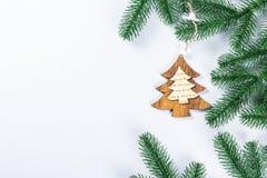Cadre de Noël avec les branches de l'arbre de Noël et des décorations en bois sur le fond blanc Composition simple W en Noël Photo libre de droits