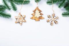 Cadre de Noël avec les branches de l'arbre de Noël et des décorations en bois sur le fond blanc Composition simple W en Noël Photographie stock libre de droits