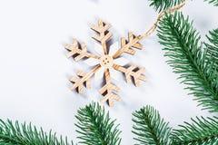 Cadre de Noël avec les branches de l'arbre de Noël et des décorations en bois sur le fond blanc Composition simple W en Noël Photographie stock