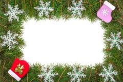 Cadre de Noël fait de branches de sapin décorées de la mitaine et de la chaussette de flocons de neige d'isolement sur le fond bl Images libres de droits