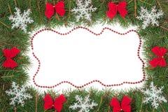 Cadre de Noël fait de branches de sapin décorées des arcs et flocons de neige d'isolement sur le fond blanc Photo libre de droits