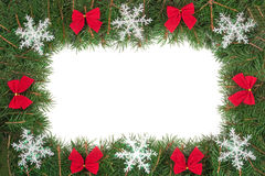 Cadre de Noël fait de branches de sapin décorées des arcs et flocons de neige d'isolement sur le fond blanc Images stock
