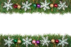 Cadre de Noël fait de branches de sapin décorées des boules colorées et flocons de neige d'isolement sur le fond blanc Photographie stock libre de droits