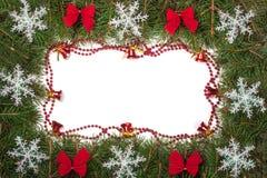 Cadre de Noël fait de branches de sapin décorées des cloches d'arcs et flocons de neige d'isolement sur le fond blanc Photos stock