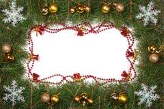 Cadre de Noël fait de branches de sapin décorées des cloches de boules et flocons de neige d'isolement sur le fond blanc Photo libre de droits