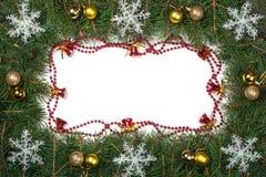 Cadre de Noël fait de branches de sapin décorées des cloches de boules et flocons de neige d'isolement sur le fond blanc Photographie stock