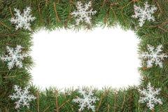 Cadre de Noël fait de branches de sapin décorées des flocons de neige d'isolement sur le fond blanc Image libre de droits