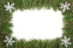 Cadre de Noël fait de branches de sapin décorées des flocons de neige d'isolement sur le fond blanc Photographie stock libre de droits