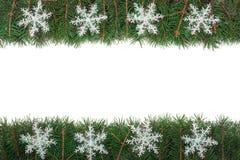 Cadre de Noël fait de branches de sapin décorées des flocons de neige d'isolement sur le fond blanc Image stock