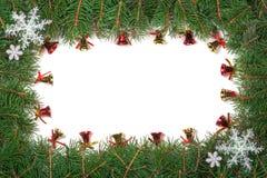 Cadre de Noël fait de branches de sapin décorées des flocons de neige et cloches d'isolement sur le fond blanc Photos libres de droits