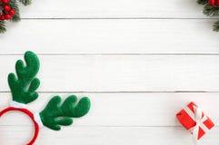 Cadre de Noël fait de feuilles de sapin, baie de houx, bandeau de Noël, et boîte-cadeau rouge sur le fond en bois blanc images stock