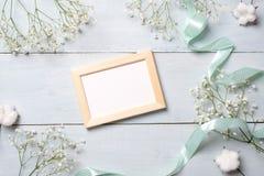 Cadre de photo de cru avec des fleurs sur le fond en bois bleu-clair Maquette de bannière pour la félicitation avec la femme ou l photo stock