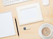 Cadre de photo sur la table de bureau avec du Cu de bloc-notes, d'ordinateur et de café Photographie stock