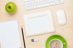 Cadre de photo sur la table de bureau avec du Cu de bloc-notes, d'ordinateur et de café Images stock