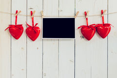 Cadre de photo vide et coeur rouge accrochant sur le fond en bois blanc Image stock