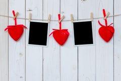Cadre de photo vide et coeur rouge accrochant sur le fond en bois blanc Image libre de droits