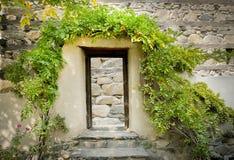 Cadre de porte en bois couvert d'arbres devant le mur en pierre photo stock
