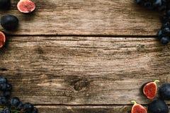 Cadre de raisin et de figue sur l'espace libre en bois moussu Photographie stock