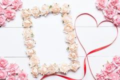 Cadre de rose de blanc avec le ruban rouge en forme de coeur au-dessus d'en bois blanc Image libre de droits