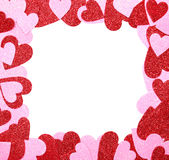 Cadre de Saint-Valentin. Coeurs de scintillement de rouge et de rose d'isolement Photo stock