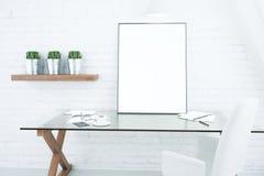 Cadre de tableau blanc vide sur la table vitreuse dans la pièce moderne de grenier, m Photos stock
