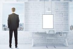 Cadre de tableau blanc vide sur le lo blanc de mur de briques et d'homme d'affaires Photos libres de droits
