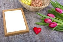 Cadre de tableau, coeur et tulipes sur un bureau en bois Image libre de droits