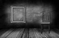 Cadre de tableau et chaise en bois dans la chambre intérieure avec le mur en pierre gris Image stock