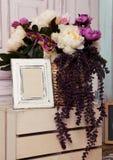 Cadre de tableau et fleurs sur la boîte en bois Photographie stock libre de droits