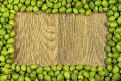 Cadre de tableau fait de jeunes noix vertes dans les cosses sur la table en bois Photos libres de droits
