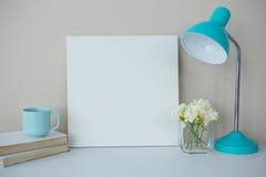 Cadre de tableau, tasse de café avec la lampe de table et vase à fleur Photo libre de droits