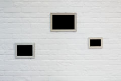 Cadre de tableau vide au mur de briques blanc Photographie stock