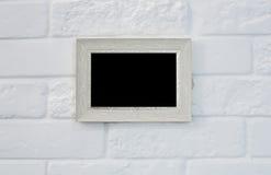 Cadre de tableau vide au mur de briques blanc Images libres de droits