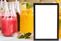 Cadre de tableau vide avec des boissons de fruit frais derrière Images stock