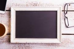 Cadre de tableau vide, lunettes, tasse de café et smartphone Images libres de droits